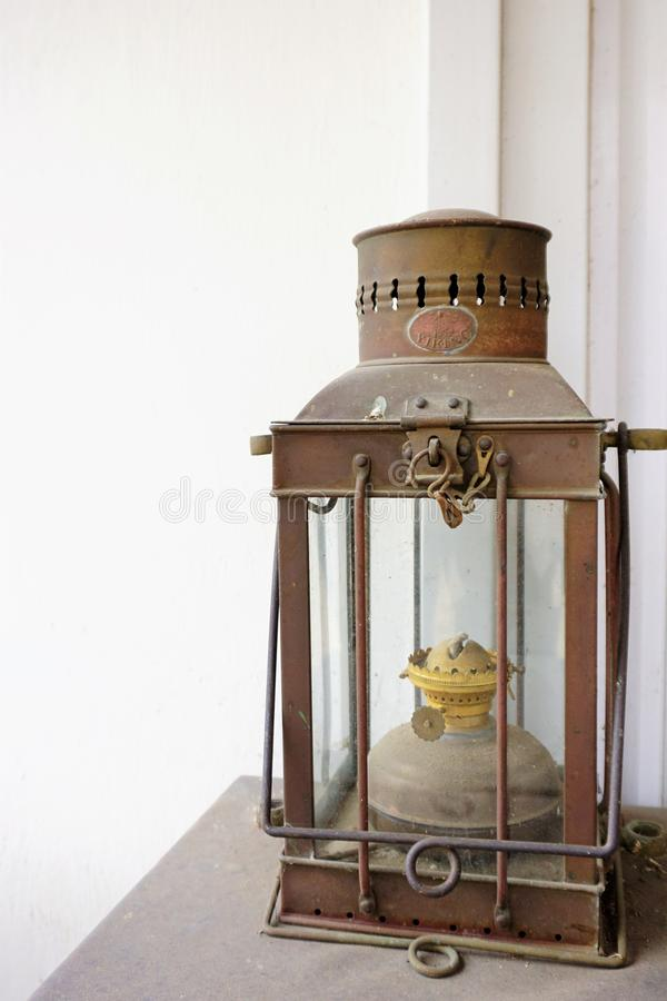 Nautical hurricane lantern dusty against white washed walls stock images