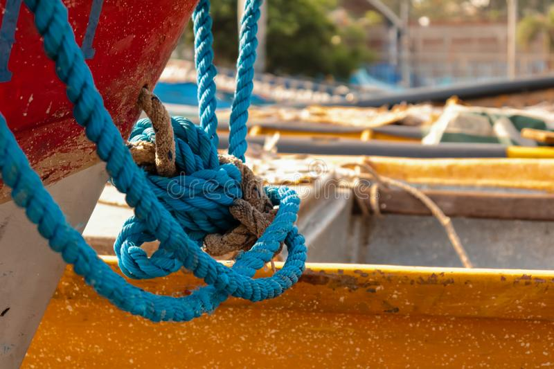 Nautical knot. Partial working boat at the marina. El Salvador. Nautical knot. Partial working boat at the marina. Knot with blue rope. Blurred marina royalty free stock photos