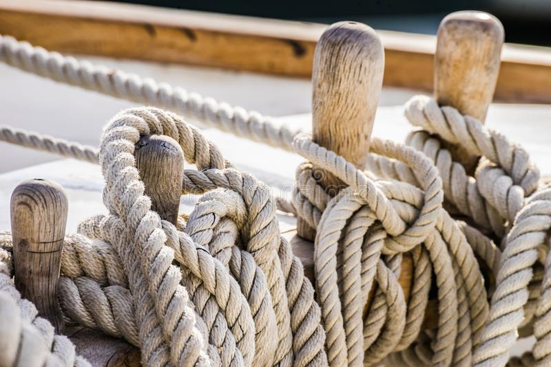 Nautical knotted ropes on wood cleats of old sailboat. Close-up of moored ropes on wooden cleats on old sailing boat yacht royalty free stock image