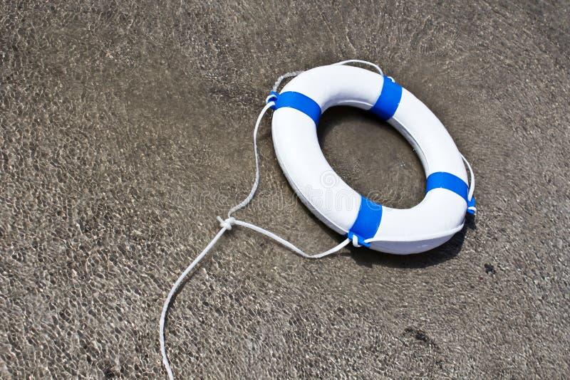 Nautical lifebuoy, lifebelt, life saver in clear water. Floating stock photo