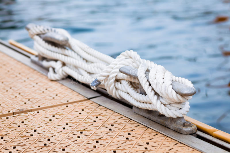 Nautical mooring rope. Close-up of a mooring rope with a knotted end tied around a cleat on a pier royalty free stock image
