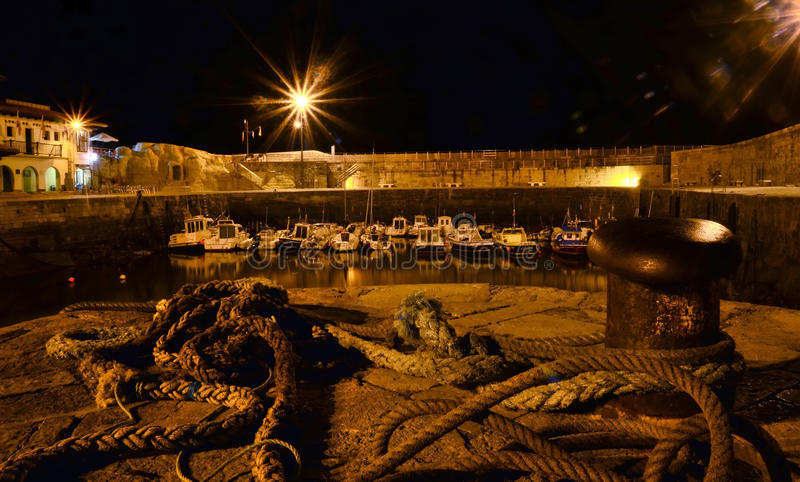 Nautical port at night. With several yachts and fishing boats in Comillas (Spain) in the bay of Biscay. Fish market in the left side, mooring bollard and ropes royalty free stock image