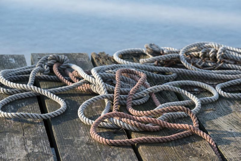 Nautical ropes on a weathered wooden jetty at the water. Selected focus, narrow depth of field stock photo