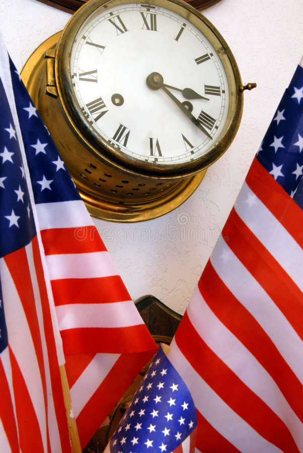 Nautical Ship's Clock and American Flags. Aged Nautical Ship's Clock and American Flags in Household Setting stock photos