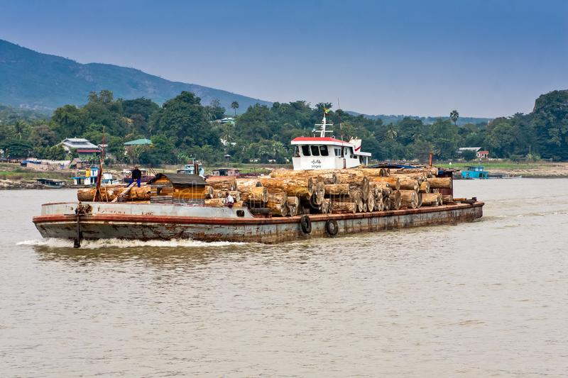Barge with wood on the Irrawaddy River near Mandalay, Myanmar. Nautical vessels are a popular mode of transportation on the Irrawaddy River royalty free stock images