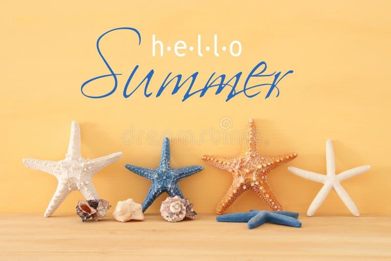 nautique, vacances et image de voyage avec des étoiles de mer au-dessus de fond et de table en bois jaunes image stock