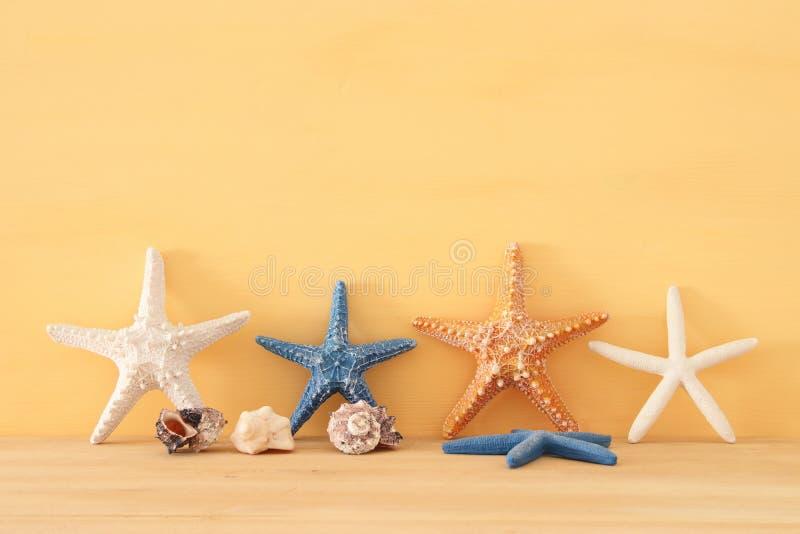 nautisch, Ferien und Reisebild mit Starfish über gelbem hölzernem Hintergrund und Tabelle lizenzfreies stockfoto