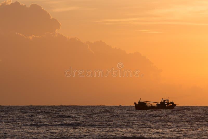 Nautisk fiskebåt i havet med härlig himmelsoluppgång arkivbilder