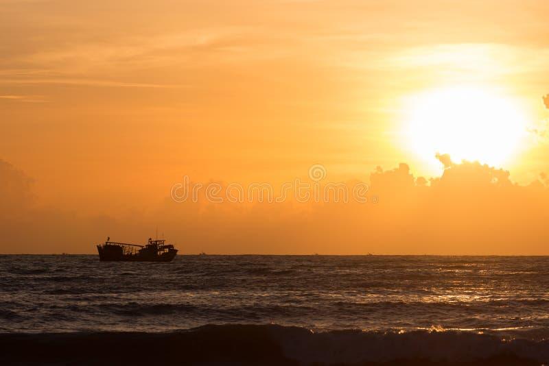 Nautisk fiskebåt i havet med härlig himmelsoluppgång royaltyfri foto