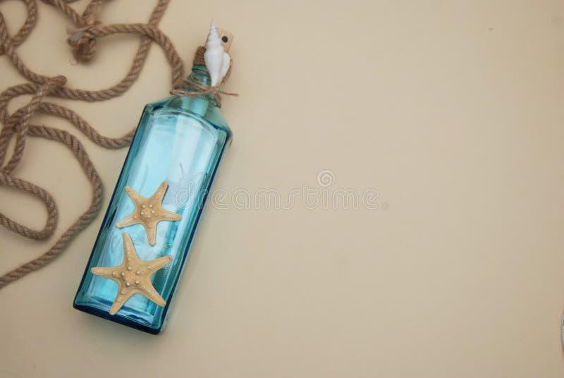 Nautisk temabakgrund, dekorativ flaska med skal, sjöstjärna på neutral elfenbenbakgrund placera text Selektivt fokusera royaltyfri foto