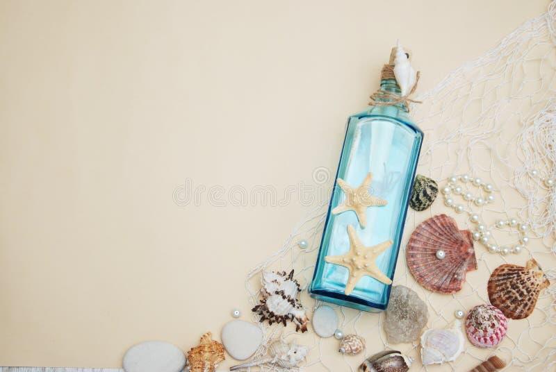 Nautisk temabakgrund, dekorativ flaska med skal, sjöstjärna på neutral elfenbenbakgrund placera text Selektivt fokusera royaltyfria bilder