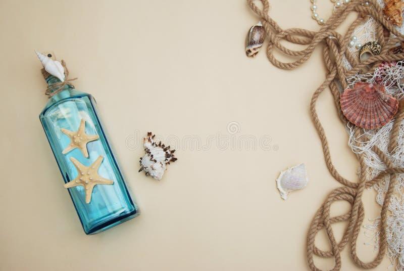 Nautisk temabakgrund, dekorativ flaska med skal, sjöstjärna på neutral elfenbenbakgrund placera text Selektivt fokusera royaltyfri bild
