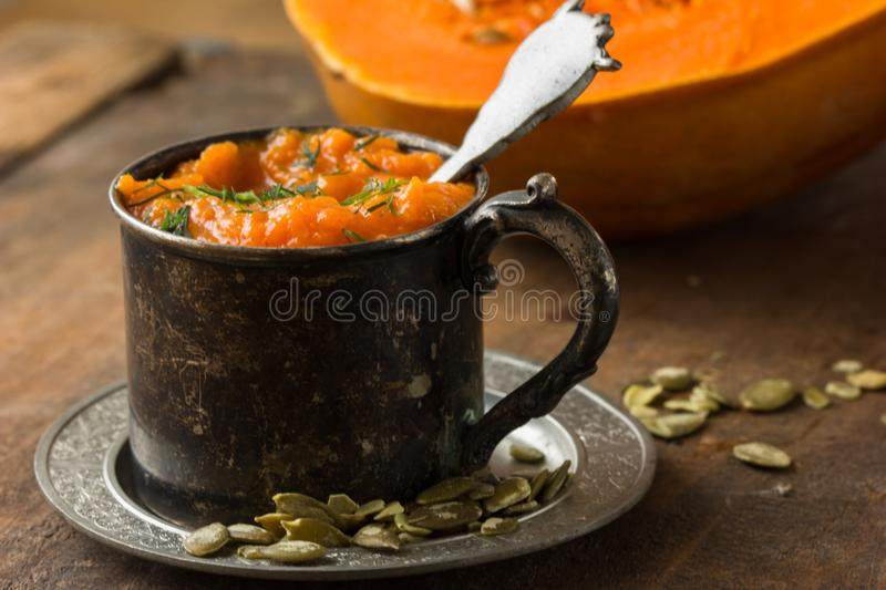 Autumn pumpkin soup with pumpkin seeds and almond, shot from above rustic wooden table royalty free stock photos