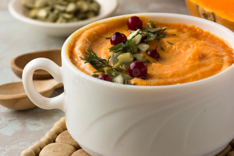 Autumn pumpkin soup with pumpkin seeds and almond, shot from above rustic wooden table stock images