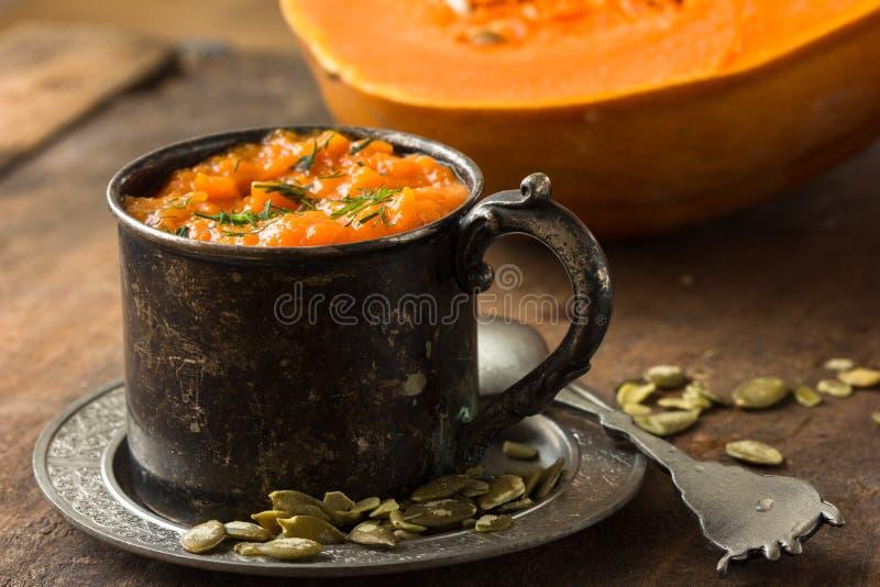 Pumpkin porridge pumpkin soup with seeds, and raw pumpkin in old mug stock photos