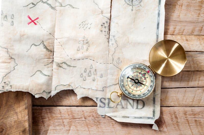 Nautyczny kompas z sfałszowaną skarb mapą abstrakcjonistyczna wyspa z czerwonym krzyżem na drewnianym stole zdjęcia stock