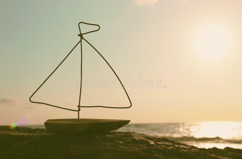 Nautyczny pojęcie z żagiel łodzią przed zmierzchu morzem i plaża krajobrazem obrazy royalty free