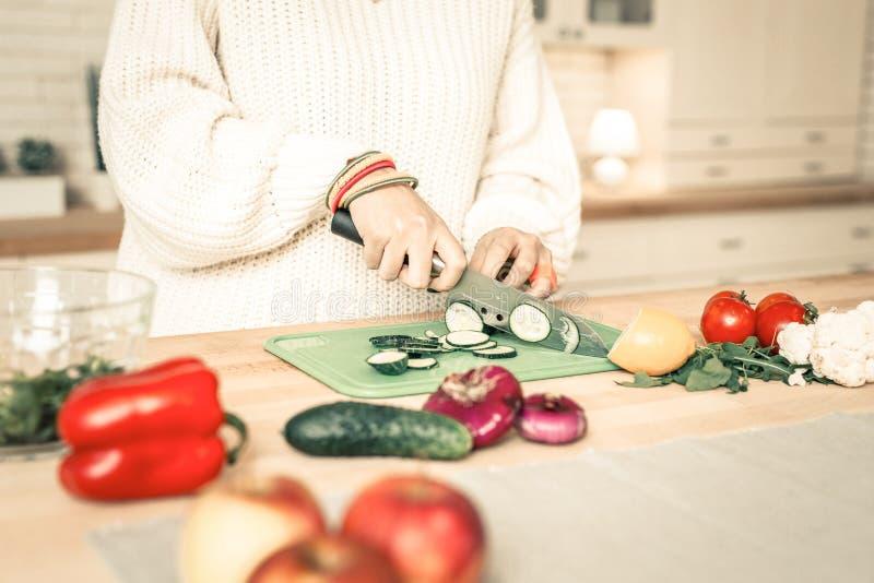 Nauwkeurige bekwame vrouwen scherpe komkommer met professioneel mes royalty-vrije stock foto's