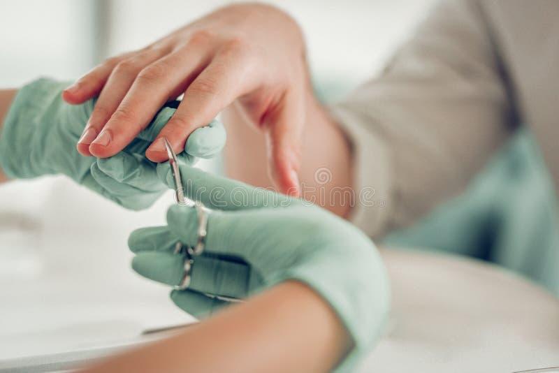 Nauwkeurige deskundige spijkermeester die in beschermende rubberhandschoenen extra huid snijden royalty-vrije stock fotografie