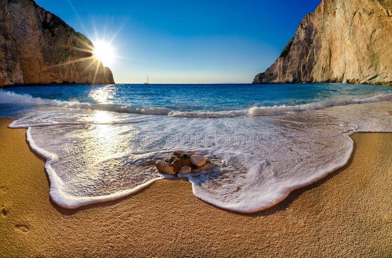 Navagio beach at sunset in Zakyntos island Greece. Navagio beach at sunset in Zakyntos island , waves with sand ,blue water in Greece royalty free stock image