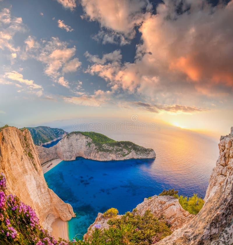 Navagiostrand met schipbreuk en bloemen tegen zonsondergang op het eiland van Zakynthos in Griekenland royalty-vrije stock fotografie