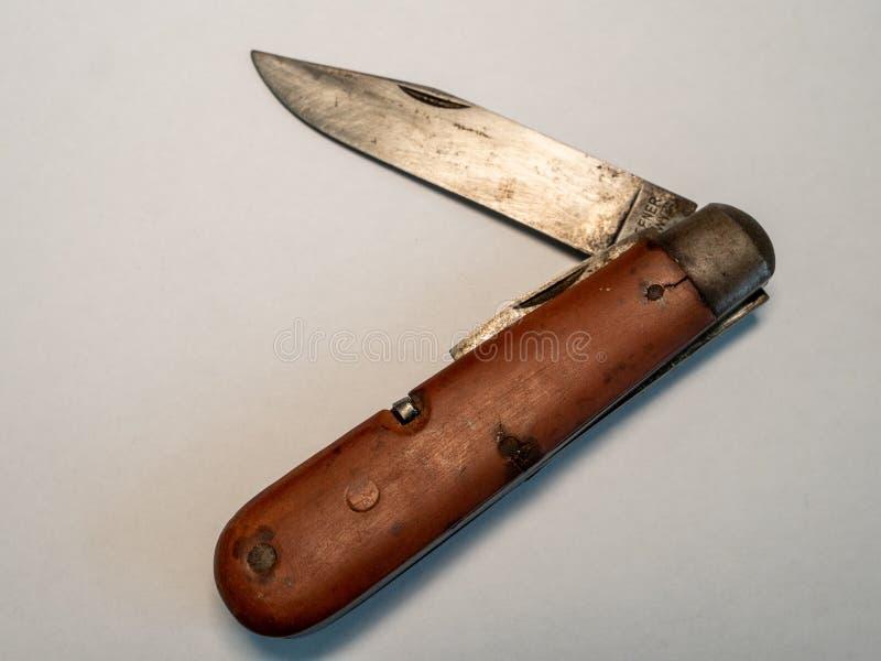 navaja de bolsillo militar antigua del vintage con el fondo usado y oxidado del blanco de la cuchilla foto de archivo