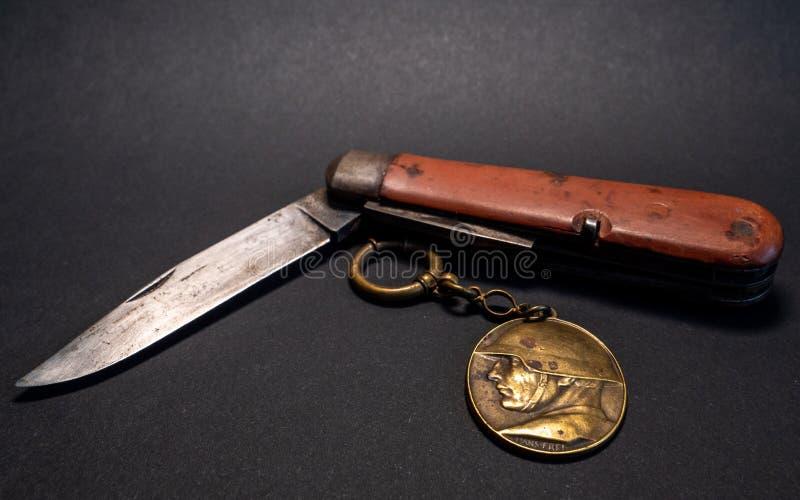 navaja de bolsillo militar suiza antigua del vintage con la guerra mundial blanca del fondo del emplem del reloj y del soldado de foto de archivo