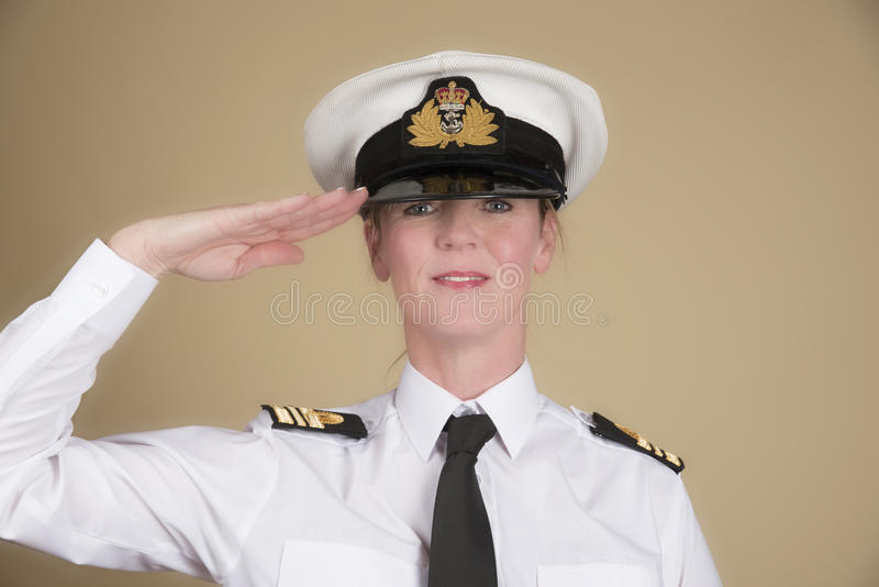 Naval officer saluting. Female navy officer in uniform of a Lt Commander saluting stock photos