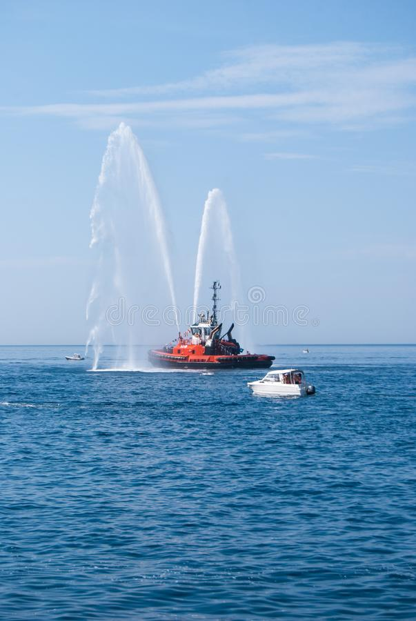 Naval vessel of firefighters with high splashes of sea water stock images