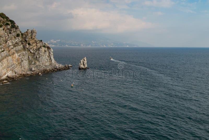 Nave à distância do mar com rochas foto de stock