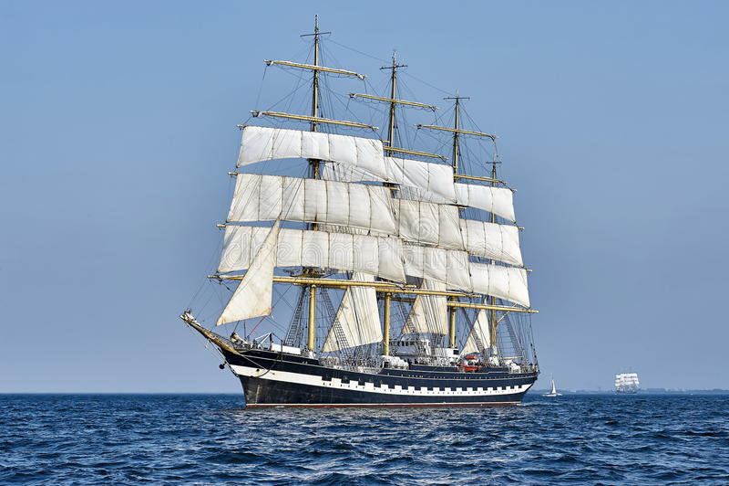 Nave alta sotto la vela con la riva fotografia stock