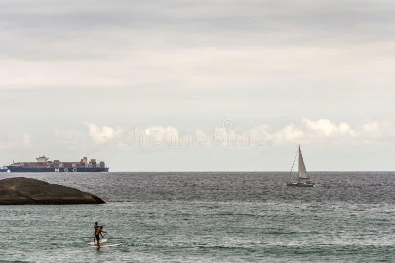 Nave, barco de navegación grandes y levantarse a la persona que practica surf de la paleta en Copacabana, Rio de Janeiro, el Bras fotos de archivo