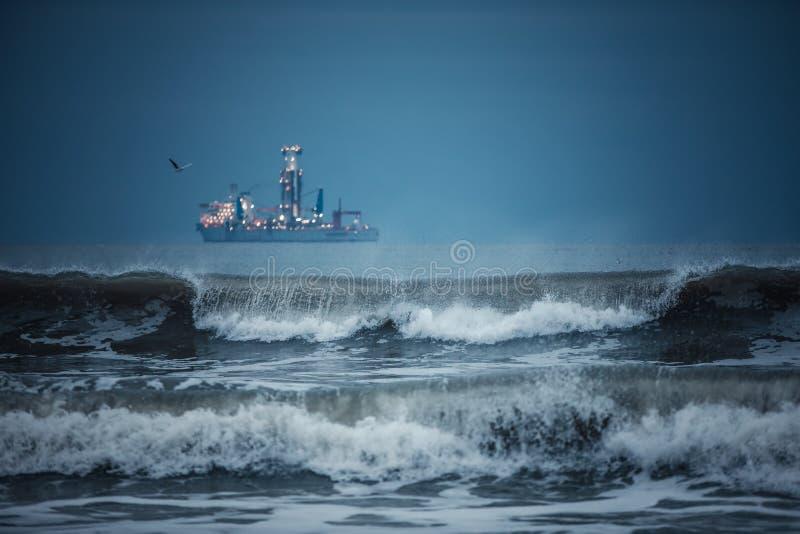 Nave da carico internazionale del contenitore nell'acqua di mare dopo il tramonto fotografia stock libera da diritti