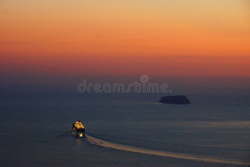 Santorini Magic Island in Greece. Nave da crociera in partenza dalla caldera di Santorini in Grecia, all`ora del tramonto, verso un viaggio nel Mediterraneo royalty free stock photo