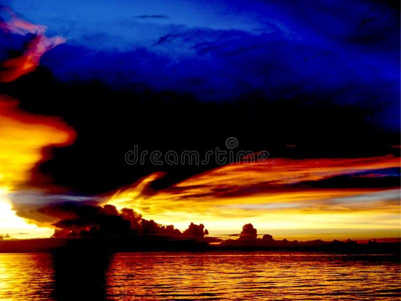 nave del mar de la puesta del sol en la línea mosca del horizonte del pájaro en la nube de noche foto de archivo
