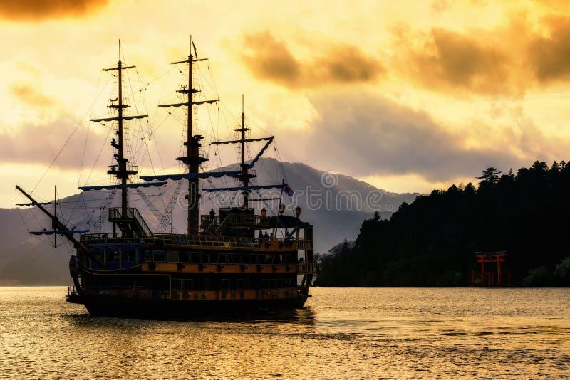 Nave di pirata della siluetta un portone di torii nel lago Ashi immagine stock