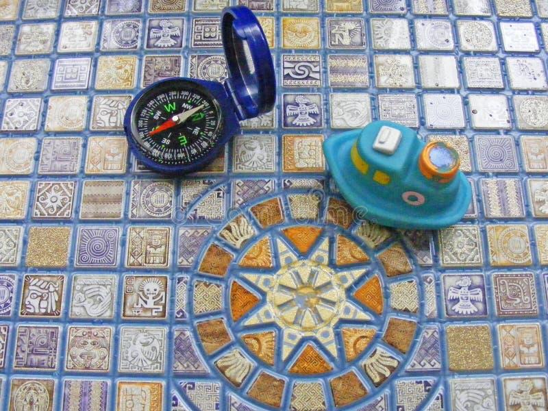 Nave e bussola concettuali del giocattolo di viaggio sul fondo del mosaico fotografie stock