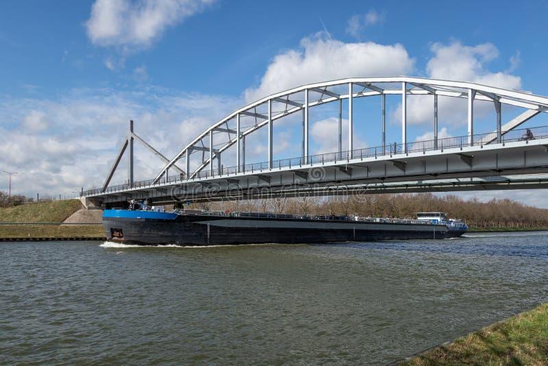 Nave en el canal holandés de Amsterdam Rijn que pasa un puente de acero imágenes de archivo libres de regalías
