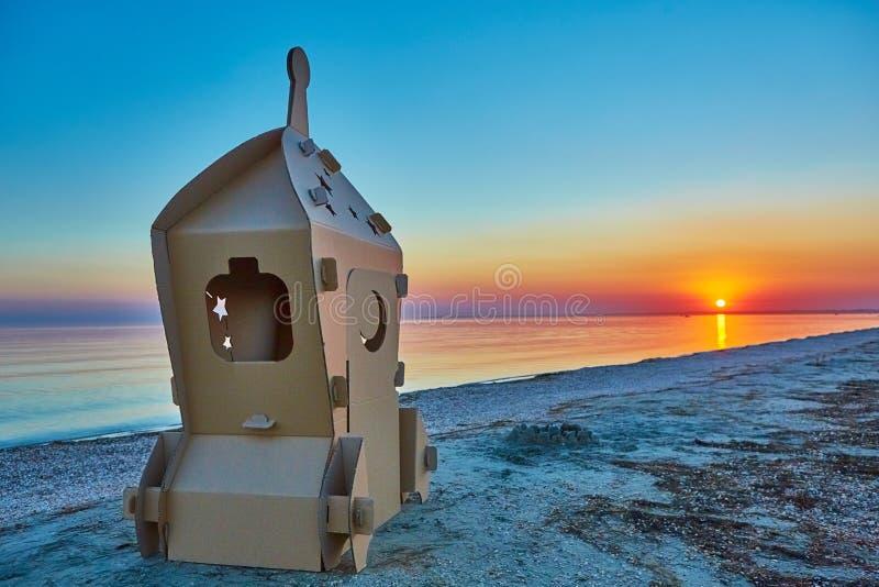 Nave espacial del juguete de la cartulina en la costa y la puesta del sol de mar imagen de archivo
