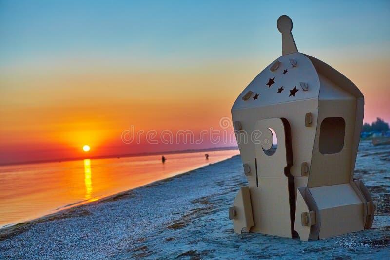 Nave espacial del juguete de la cartulina en la costa y la puesta del sol de mar imagen de archivo libre de regalías