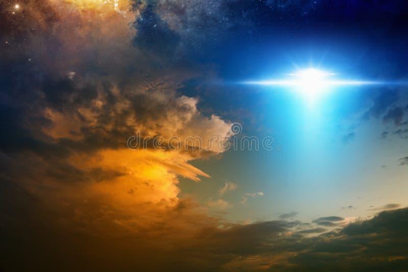 Nave espacial extraterrestre dos estrangeiros no céu de incandescência vermelho do por do sol foto de stock