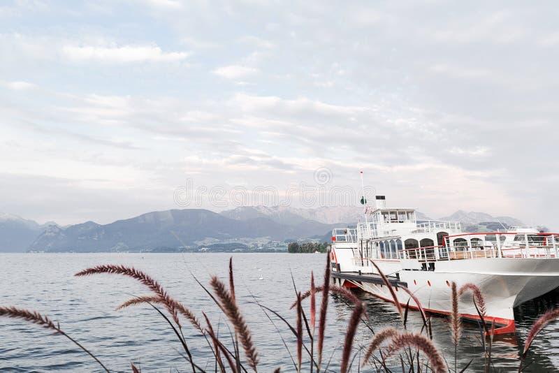 Nave facente un giro turistico bianca attraccata al pilastro sui precedenti del lago e delle montagne fotografia stock libera da diritti