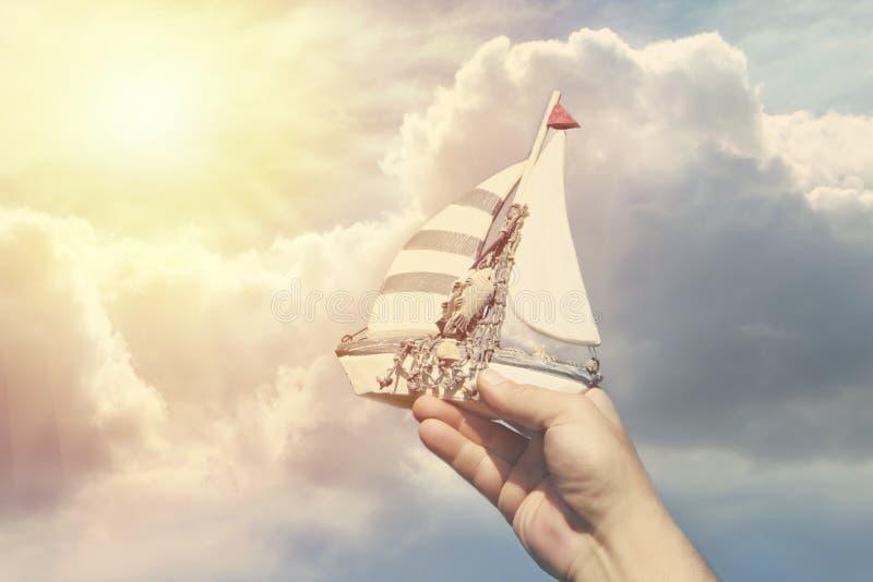 Nave hecha a mano en una mano del ` s del hombre contra un fondo de nubes como símbolo del viaje y de sueños foto de archivo libre de regalías