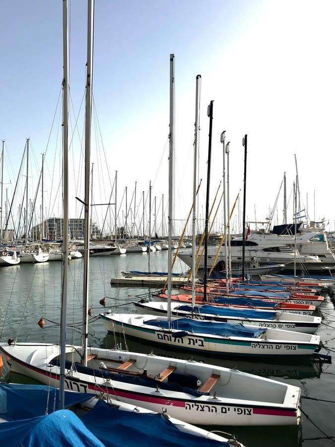 Nave hermosa del yate amarrada en el puerto con otros barcos en el mar salado azul fotos de archivo