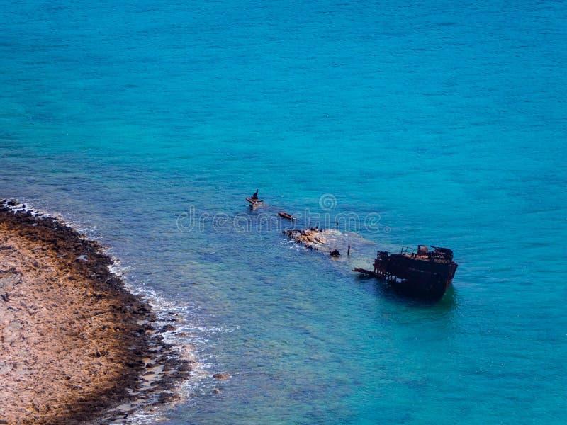 Nave hundida vieja cerca de la orilla rocosa - agua azul hermosa fotos de archivo libres de regalías