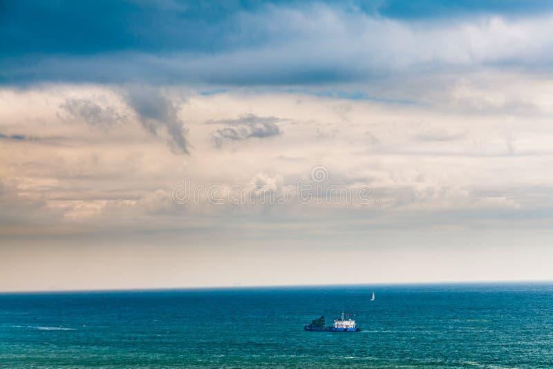 Nave sola en el mar azul imagenes de archivo