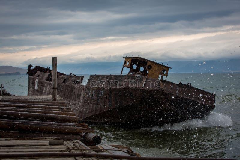 Nave vieja, oxidada cerca del embarcadero Las ondas grandes inundan la cubierta Tarde nublada del verano imágenes de archivo libres de regalías