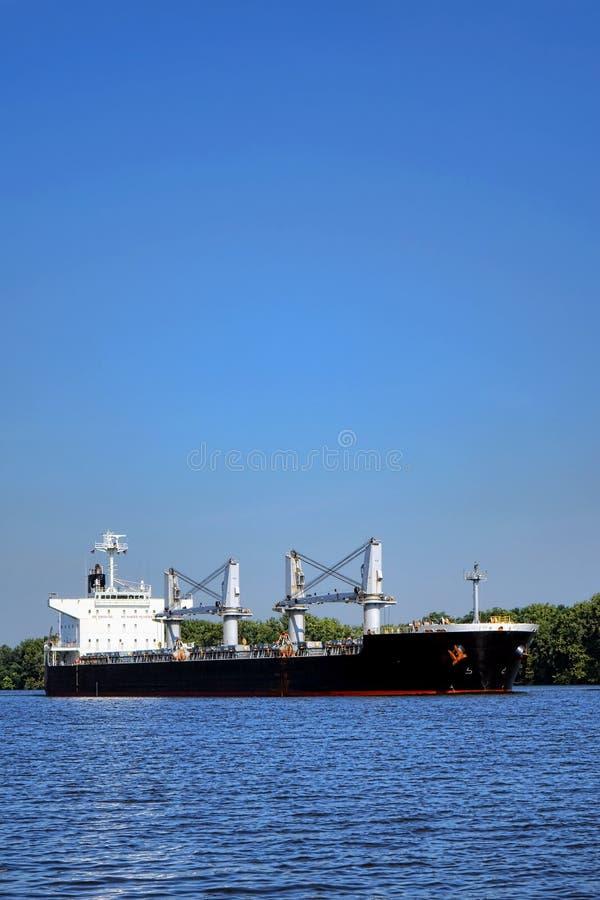 Navegación cargada del buque de carga del portador de carga en el río imagen de archivo