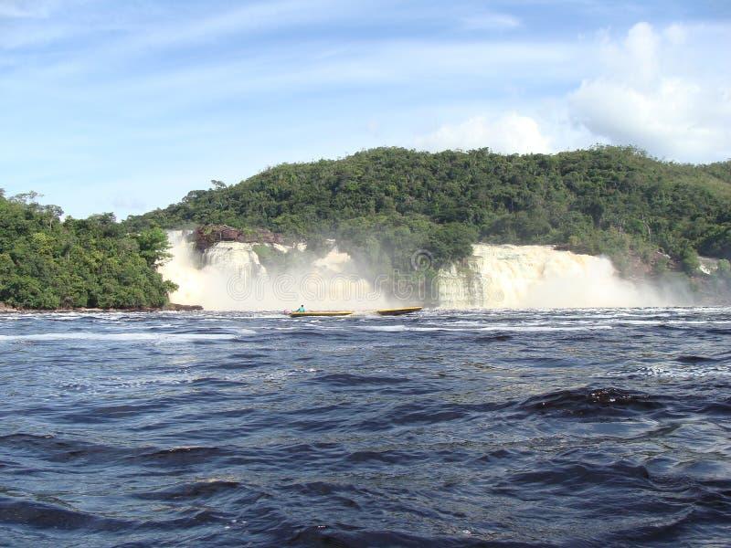 Navegación de la laguna delante de las cascadas foto de archivo