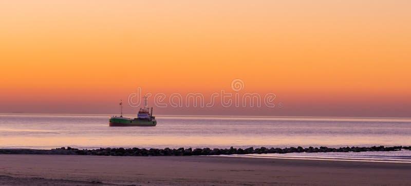 Navegación de la nave encendida en el mar en la puesta del sol, la costa belga, la naturaleza y el fondo del transporte fotografía de archivo